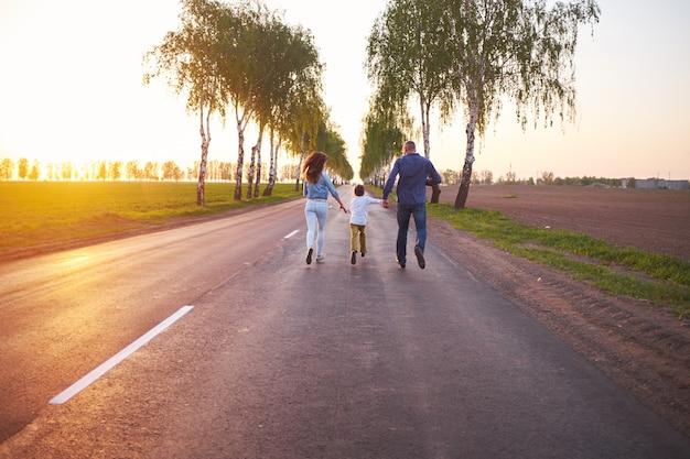 Família feliz pai mãe e filho brincando ao ar livre na estrada perto do campo,