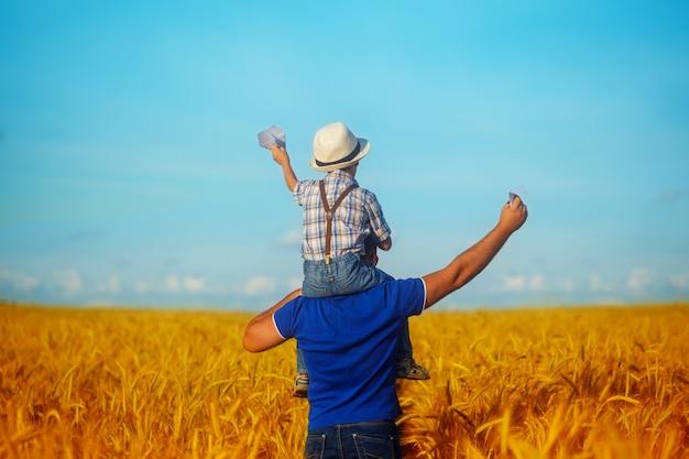 Família feliz: pai novo com seu filho pequeno que anda no campo de trigo no por do sol em um dia de verão morno. vista traseira