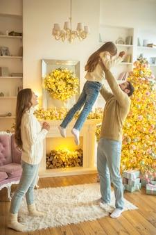 Família feliz. pai segurando a filha no ar e se sentindo feliz