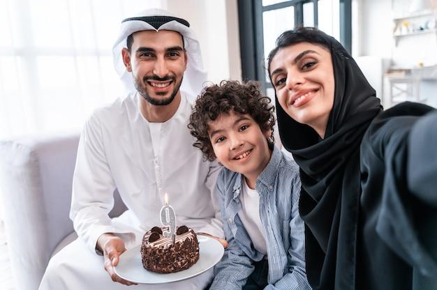 Família feliz, pais árabes e criança comemorando aniversário juntos