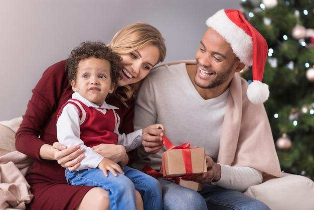 Família feliz. pais jovens e positivos sentados no sofá olhando para o filho enquanto comemoram o natal