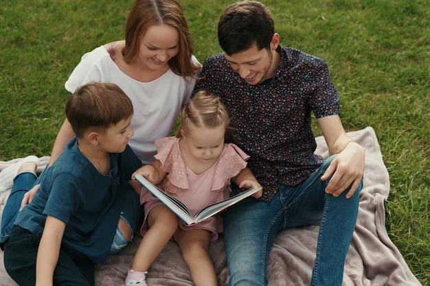 Família feliz passa tempo juntos lendo um livro no parque