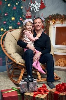 Família feliz passa tempo juntos nas férias de inverno em casa junto à lareira perto da árvore de natal com presentes. menina bonitinha com o pai na cadeira na árvore de natal.