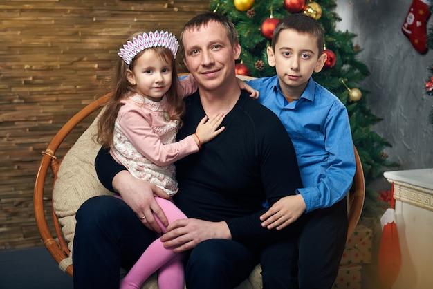 Família feliz passa tempo juntos nas férias de inverno em casa junto à lareira perto da árvore de natal com presentes. menina bonitinha e menino com seu pai na cadeira na árvore de natal.