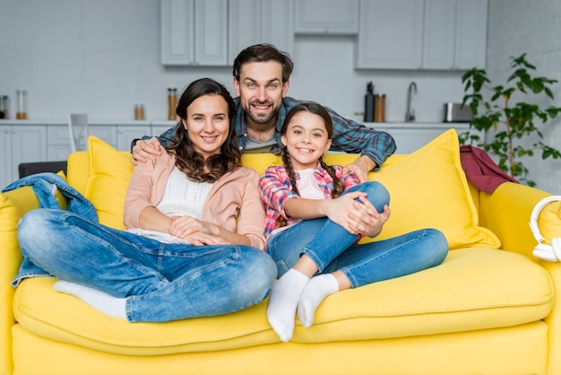 Família feliz passa tempo juntos no sofá
