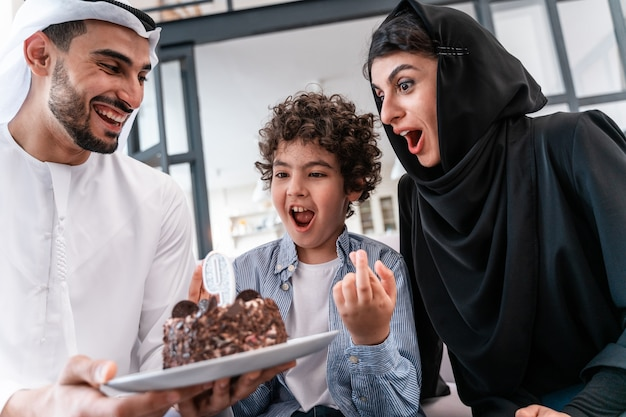 Família feliz, passando algum tempo juntos. pais árabes e criança comemorando aniversário juntos