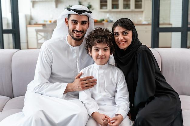 Família feliz, passando algum tempo juntos. pais árabes e seu filho brincando e fazendo diversas atividades em casa
