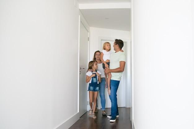 Família feliz passando pelo corredor de sua nova casa