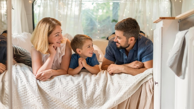 Família feliz passando um tempo na cama em uma caravana