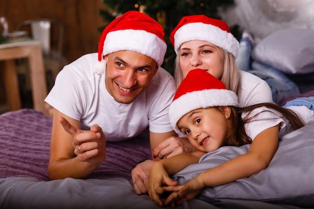 Família feliz perto da árvore de natal. criança, mãe e pai se divertindo em casa