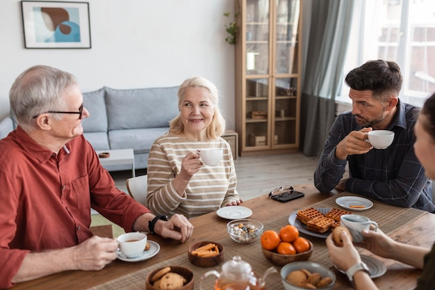 Família feliz perto da mesa