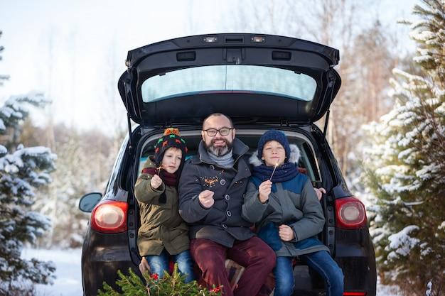 Família feliz perto de carro preto no dia de inverno nevado. férias de conceito.