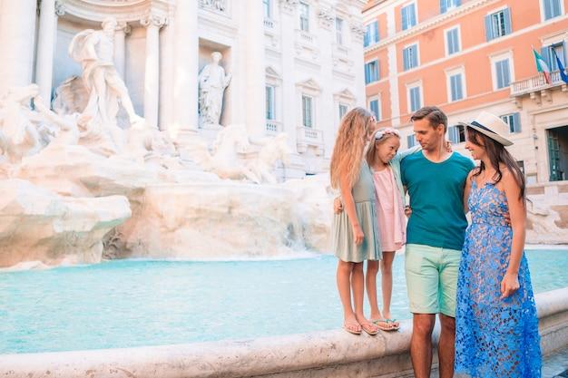 Família feliz perto de fontana di trevi com mapa da cidade