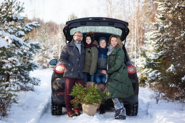Família feliz perto de um carro preto na floresta de neve de inverno