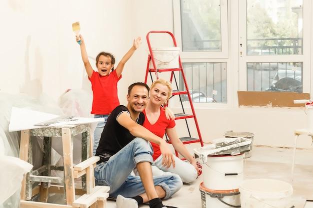 Família feliz pintando uma parede em casa