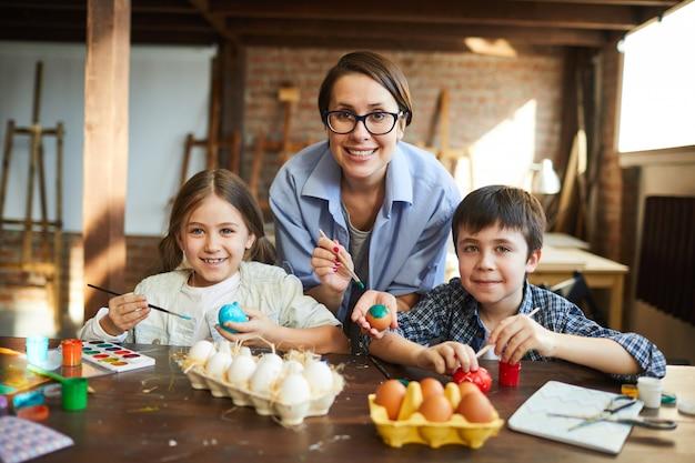 Família feliz pintura ovos páscoa