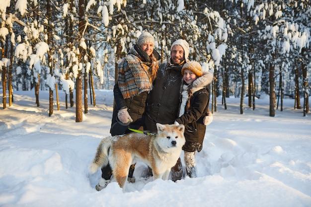 Família feliz posando com cachorro no inverno