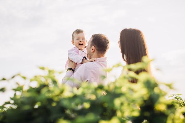 Família feliz posando em um campo verde