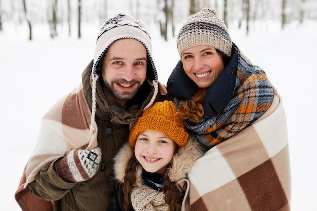 Família feliz posando na floresta de inverno
