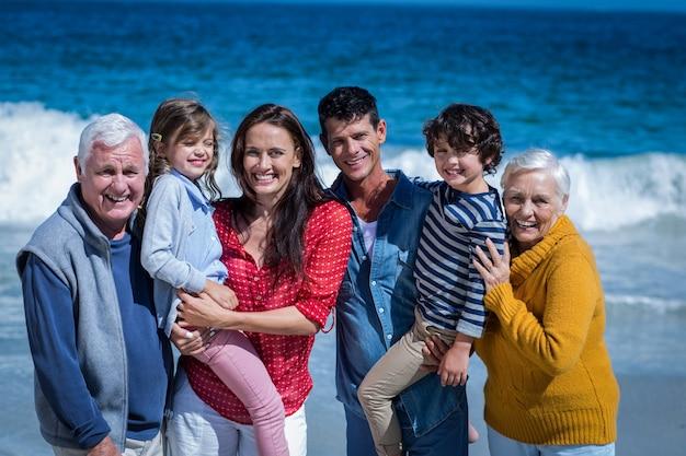 Família feliz posando na praia
