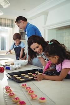 Família feliz preparando biscoitos na cozinha