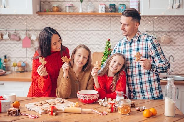 Família feliz preparando biscoitos para o natal na cozinha