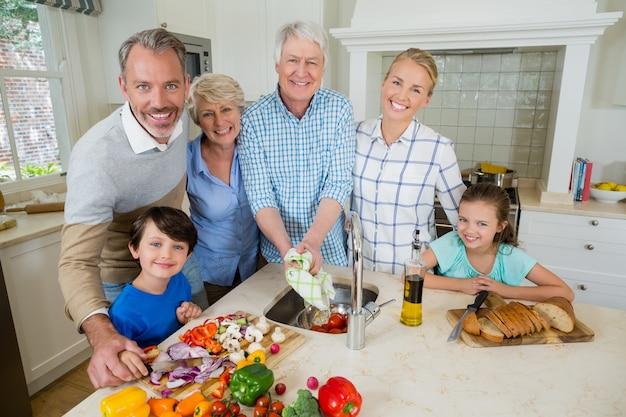 Família feliz preparando comida na cozinha