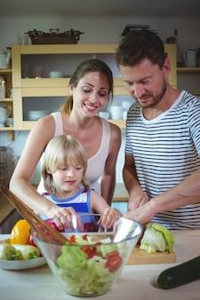 Família feliz preparando salada na cozinha