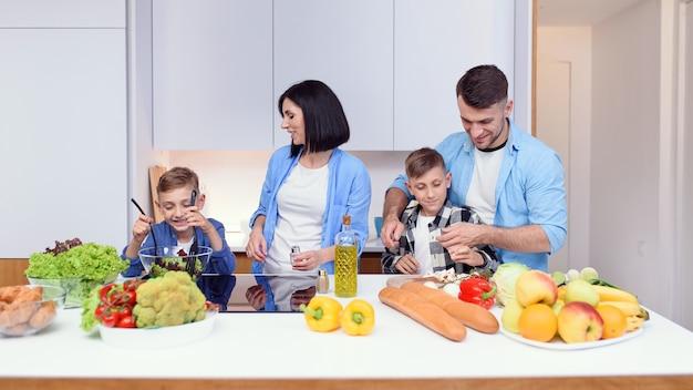 Família feliz preparando um café da manhã vegetariano saudável com legumes na cozinha