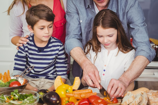 Família feliz, preparando uma salada de legumes