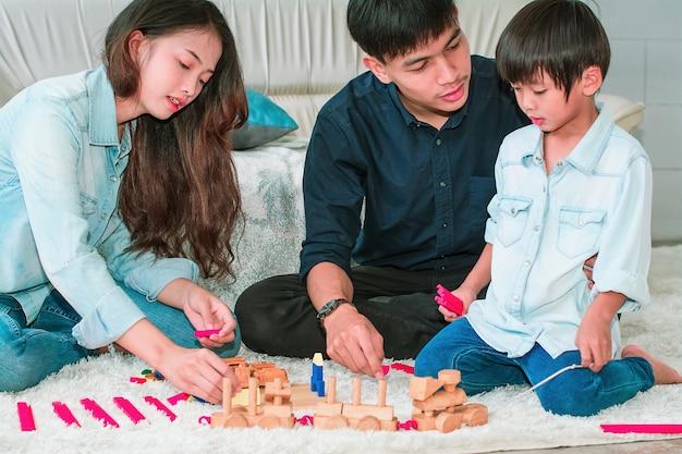 Família feliz que joga com o brinquedo em casa.