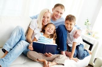 Família feliz que lê um livro