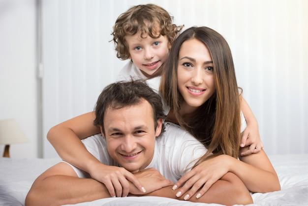 Família feliz que olha a câmera em sua cama.