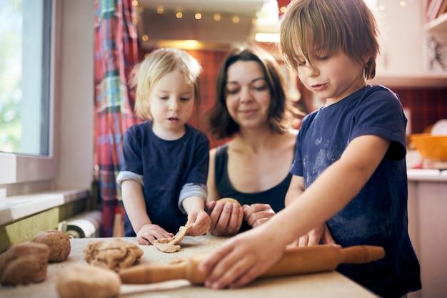 Família feliz rapazes engraçados e sua mãe estão preparando a massa