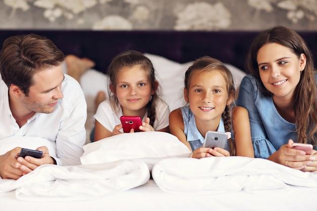 Família feliz relaxando em quarto de hotel