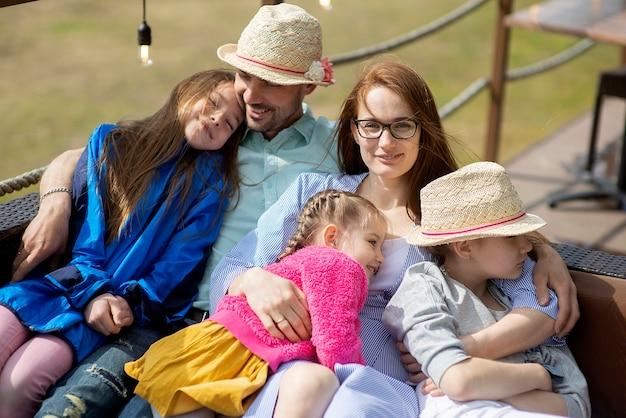 Família feliz relaxando no restaurante de verão do terraço ao ar livre