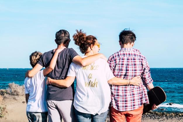 Família feliz reunida e abraçada em frente à praia e olhando o mar - quatro pessoas - criança e adolescente - milenar com prancha de skate no braço