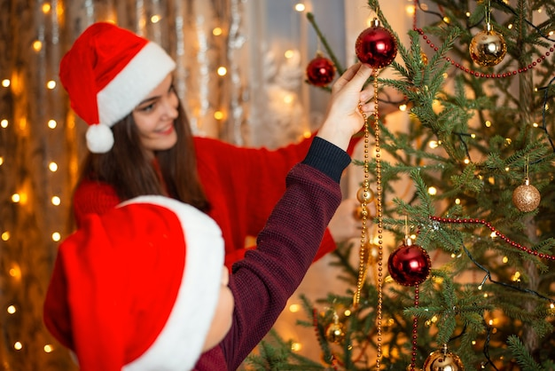 Família feliz reunida em casa decorando árvore de natal