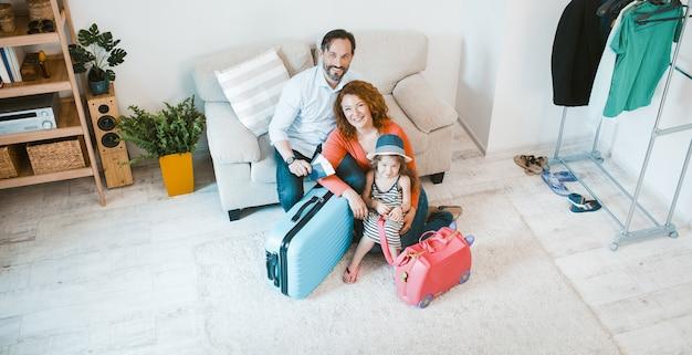 Família feliz, saindo de férias, sentado no sofá com malas.