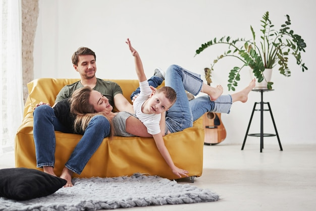 Família feliz se diverte no sofá amarelo da sala de estar de sua nova casa.