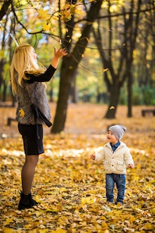 Família feliz se divertindo ao ar livre no parque outono contra folhas desfocadas