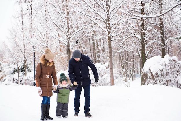 Família feliz se divertindo e brincando com a neve na floresta