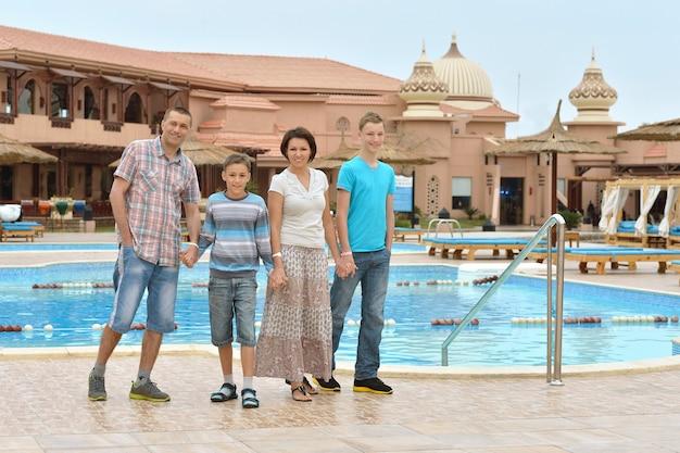 Família feliz se divertindo em um resort tropical perto da piscina.