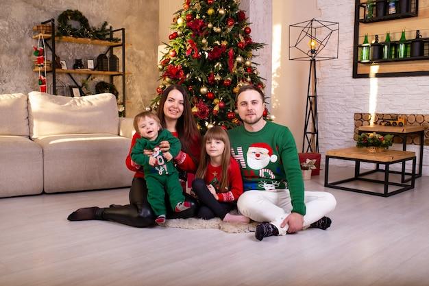 Família feliz se divertindo juntos em casa perto de árvore de natal em