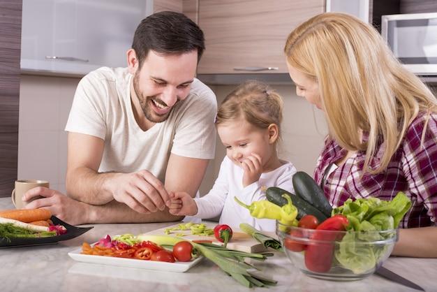 Família feliz se divertindo na cozinha enquanto prepara uma salada de legumes fresca