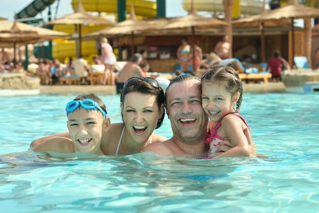 Família feliz se divertindo na piscina com o polegar para cima