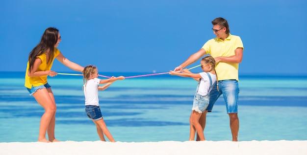 Família feliz se divertindo na praia branca