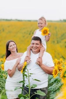 Família feliz se divertindo no campo de girassóis. pai segurando sua filha. menina segurando girassol. tiro ao ar livre. foco seletivo.