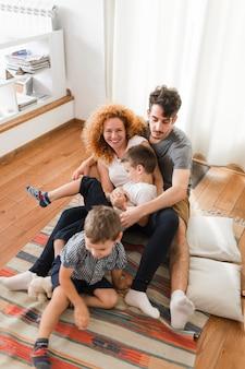 Família feliz se divertindo no tapete