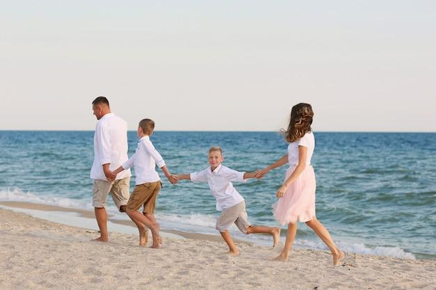 Família feliz se divertir caminhando na praia.